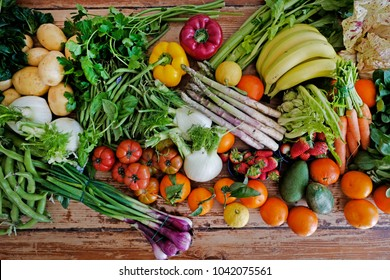 Italian fresh seasonal fruits and vegetables on a wooden kitchen table