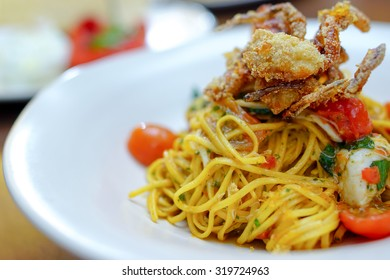 Italian fusion food - pan fried spaghetti with olive oil with crab and topping with deep fried soft shell crab