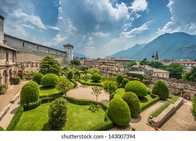 Italian Garden of Buonconsiglio in Trento, Trentino, Italy. It is a beautiful summer day. The mountains are visible in the background.