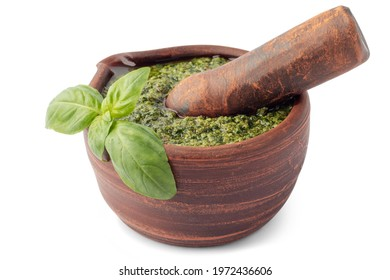 Italian green pesto sauce in clay mortar with pestle isolated on white background. Traditional Mediterranean cooking