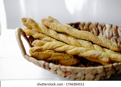Italian grissini or salted breadsticks. sesame breadsticks in a craft paper on white wooden table. close up view