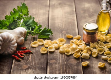 Italian handmade pasta Orecchiette with turnip leaves and tops or cima di rapa with salt anchovies, chili pepper, olive oil, garlic.  Southern Italy food rustic background, Puglia, Bari