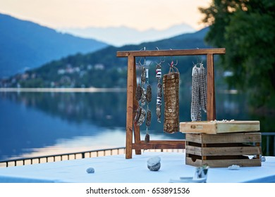Italian hand-made rustic pepperoni and salami hanging by the mountain lake