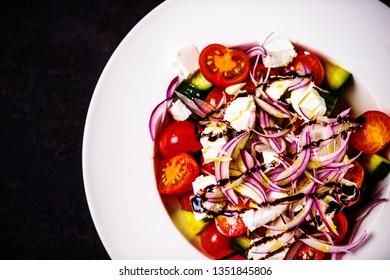 Italian homemade traditional salad with tomato mozzarella onion cucumber
