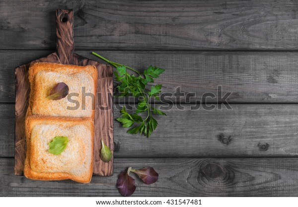 Italian hot crispy toasted panini sandwiches closed on a cutting board, lettuce, parsley on gray wooden background, top view