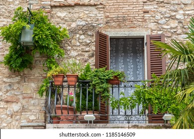 Italian house with balcony and plants.  The window has shutters. In Sirmione, Lake Garda