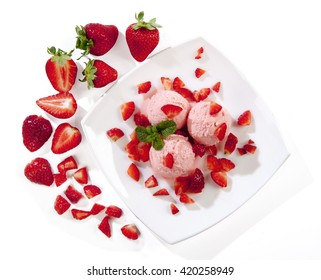 Italian ice cream with strawberry pieces of strawberries served on a plate viewed from above