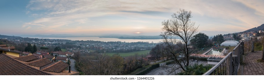Italian lake at sunset. Aerial and panoramic view of Varese lake, province of Varese, northern Italy. Is  frequented for fishing, rowing, walking and cycling along the 28 km cycle path