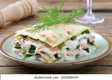 italian lasagna with salmon and spinach on rustic background