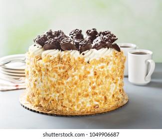 Italian layered almond cake with chocolate cannoli on top