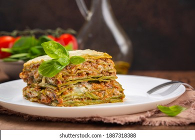 Italian lunch: homemade green lasagna with spinach in the dough, ragu - meat sauce, bechamel and parmesan cheese. Fresh salad and botle of olive oil on dark brown  background.