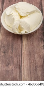 Italian mascarpone cream cheese in white bowl over wooden background