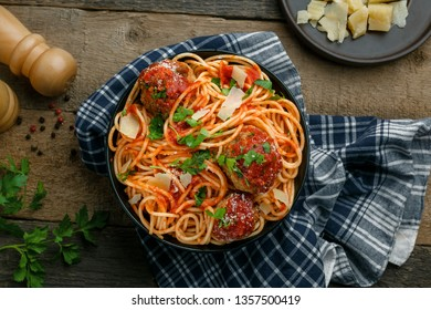 Italian meal made of pasta on a wooden table. Traditional American spaghetti with meatballs and tomato sauce in a bowl. Top view shot.