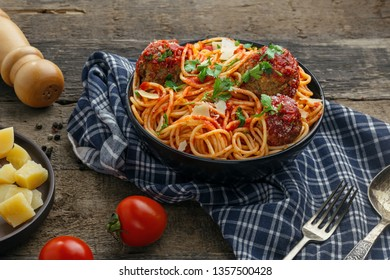 Italian meal made of pasta on a wooden table. Traditional American spaghetti with meatballs and tomato sauce in a bowl.