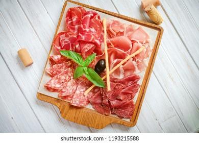 Italian meat antipasti set on wooden surfaces, jamon, prosciutto, salami, ham