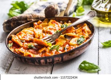 Italian or mediterranean food pasta ravioli of tomato sauce and basil.