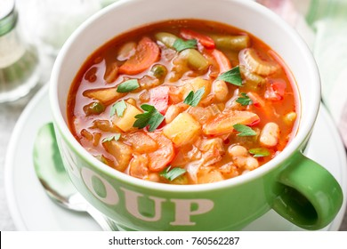 Italian minestrone soup in bowl on gray stone background. Selective focus.