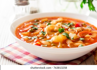 Italian minestrone soup on white wooden background. Selective focus.
