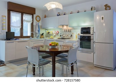 Italian modern white home kitchen interior with round wooden table and tiled floor