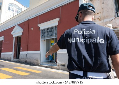 An Italian municipal policeman gestures towards traffic with polizia municipale(municipal police) on his uniform.A yellow pedestrian crossing is visible.Italy - Image