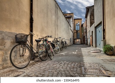 italian narrow street in the decadent old town - bicycles in a grunge dark alley in Italy