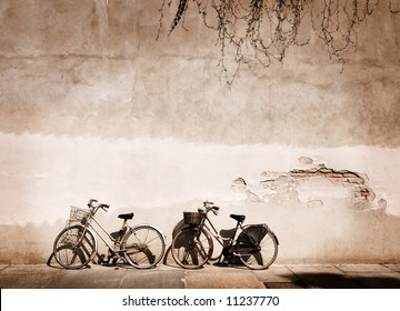 Italian old-style bicycles leaning against a wall in the historic centre of Parma