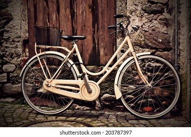 Italian old-style vintage yellow bicycle with the basket standing against a grunge wall under a wooden door