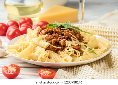 Italian pasta bolognese penne rigatone minced meat in tomato sauce and parmesan cheese. Still life on white wooden table served with cherry tomatoes, carafe of olive oil and glass of white wine