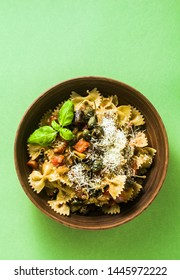 italian pasta butterflies with sicilian vegetable caponata in a clay plate on a green background