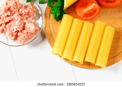 Italian pasta cannelloni. Raw tube for stuffing stuffing surrounded by ingredients for cooking, parmesan cheese, tomato, minced meat on a white wooden table. Top view. Copy the space