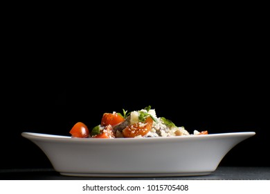 Italian pasta with cheese, cherry and basil on a black background