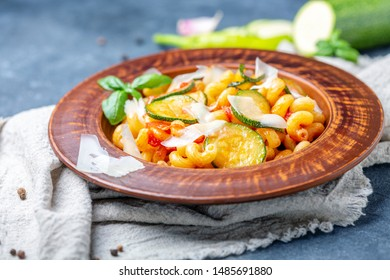 Italian pasta with courgettes, tomatoes and Parmesan in a ceramic plate on homespun linen fabric, selective focus.