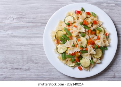 Italian pasta farfalle with slices of vegetables on a wooden background. horizontal top view