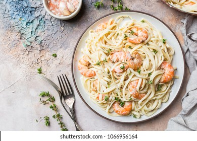 Italian pasta fettuccine in a creamy sauce with shrimp on a plate, top view