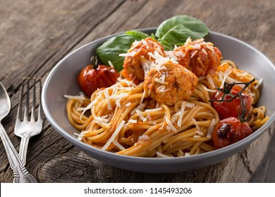 Italian pasta with meatballs, cheese, tomatoes, basil. Pasta served on a old wooden table with green napkin, spoon and knife.