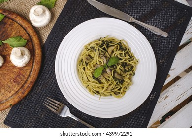 Italian pasta with mushrooms, spinach, pesto and parmesan - top view