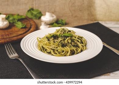 Italian pasta with mushrooms, spinach, pesto and parmesan