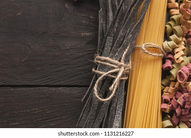 Italian pasta with natural colorings and cooking ingredients on dark wooden background, copy space.