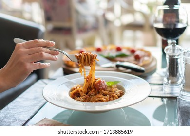Italian pasta on a fork in a white plate with pizza in the background