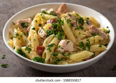 Italian pasta penne with chicken meat and bacon on plate