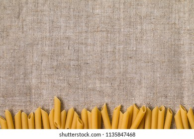Italian pasta penne on a gray background. Raw macaroni with a blank placard for text