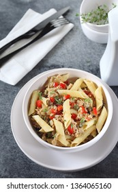 Italian pasta penne salad with tuna, bell pepper and cappers on dark background