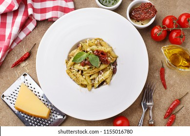 Italian pasta penne with sun dried tomatoes, pine nuts, beans, pesto sauce and basil leaves on beige concrete background. Top view