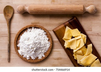 Italian pasta. Rolling pin, flour, ladle. Wooden surface. Some ingredients to make Italian pasta. Flour and pasta. All on a wooden surface. Flour in a plate of cork.