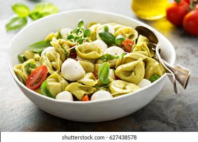 Italian pasta salad with spinach ricotta tortellini, mozzarella, tomatoes and basil