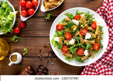 Italian pasta salad with wholegrain fusilli, fresh tomato, cheese, lettuce and broccoli on wooden rustic background. Mediterranean cuisine. Cooking lunch. Healthy diet food. Top view
