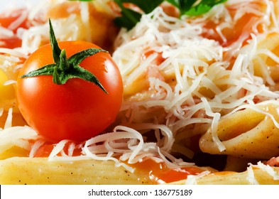 Italian pasta with sauce and parmesan cheese, served on a white plate