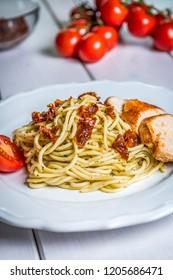 Italian pasta spaghetti with chicken, sundried tomato and basil pesto on white table