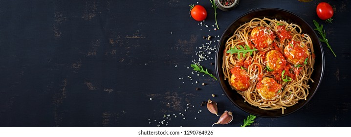 Italian pasta. Spaghetti with meatballs and parmesan cheese in black plate on dark rustic wood background.  Dinner. Top view. Banner. Slow food concept