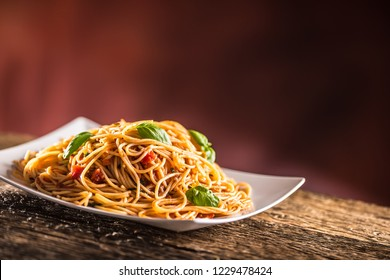 Italian pasta spaghetti with tomato sauce basil and parmesan cheese in white plate.